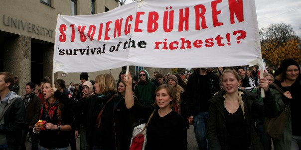 MUNICH, GERMANY - NOVEMBER 17: Students hold a poster reading 'Tuition fees survival of the richest' as they walk past the university of technology during a protest march on November 17, 2009 in Munich, Germany. Following massive protests this summer German students across the country return to the streets to demonstrate against the alleged failings of the educational system. (Photo by Miguel Villagran/Getty Images)