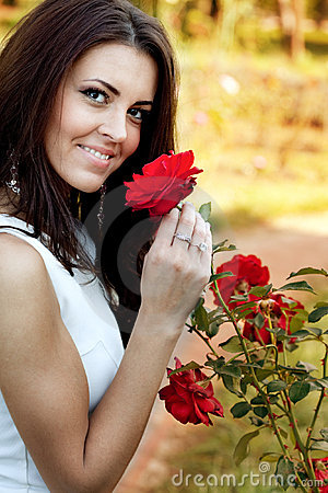 woman-flower-garden-smelling-red-roses-13755220